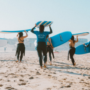 Surfers enjoying with the surf camp friends on the beach